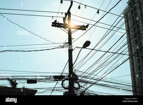 small resolution of low angle view of concrete post for street lamp and electric wires at dusk thick network of cables in silhouette hanging on a pole in panama city co