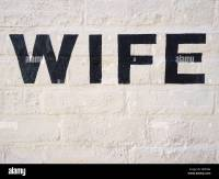 Wife written in black paint on white painted brick wall ...