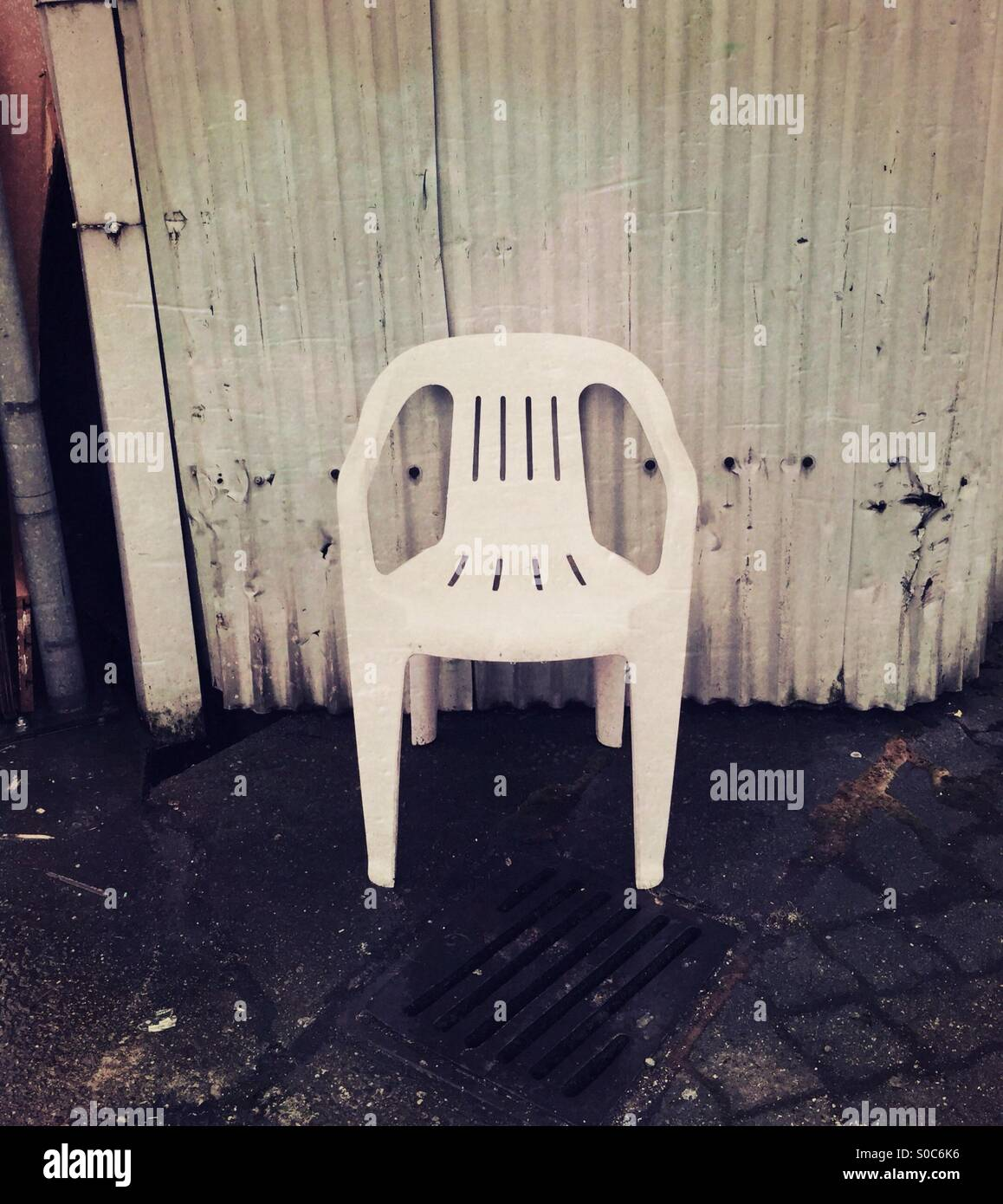 Old White Plastic Patio Chair Against Corrugated Metal Wall