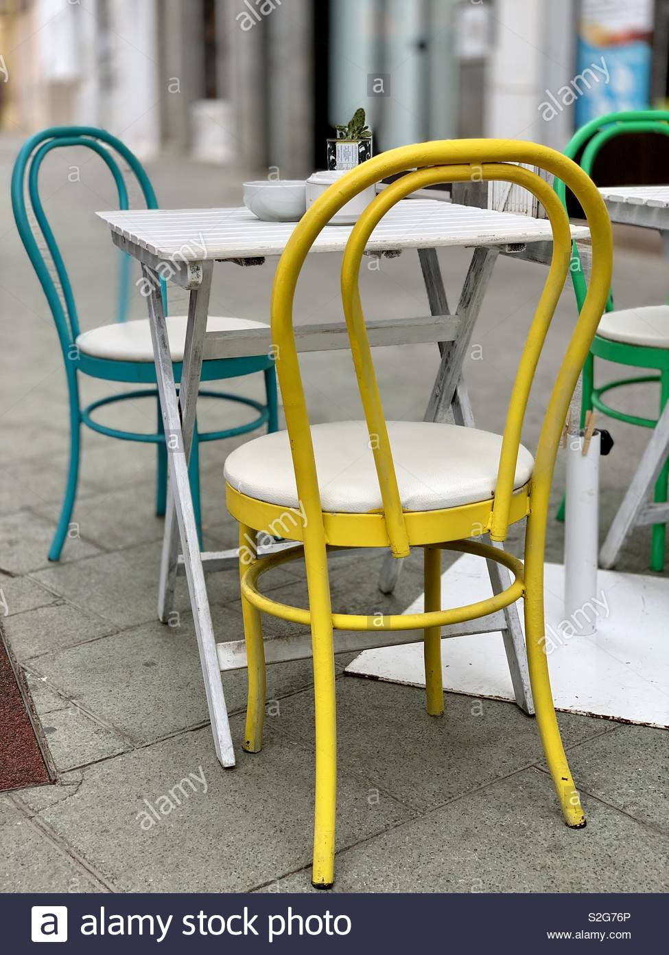 Metal Chairs Yellow Blue And Green Metal Chairs And White Table On The Street