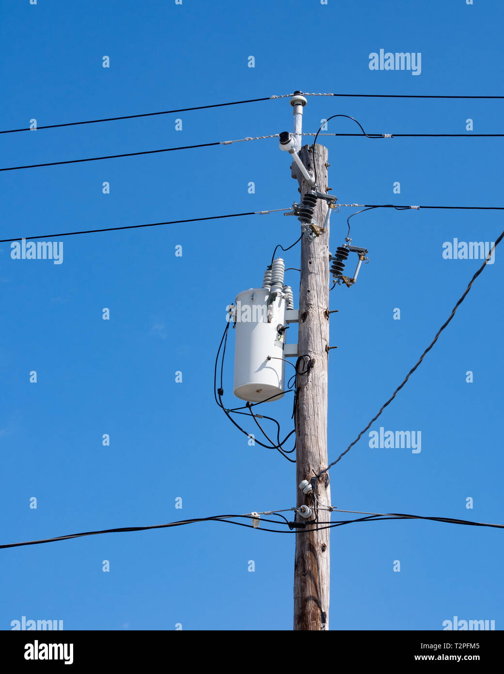 hight resolution of an electric transformer and transmission wires cable tv and telephone wires attached to an old wooden power pole with a deep blue sky background