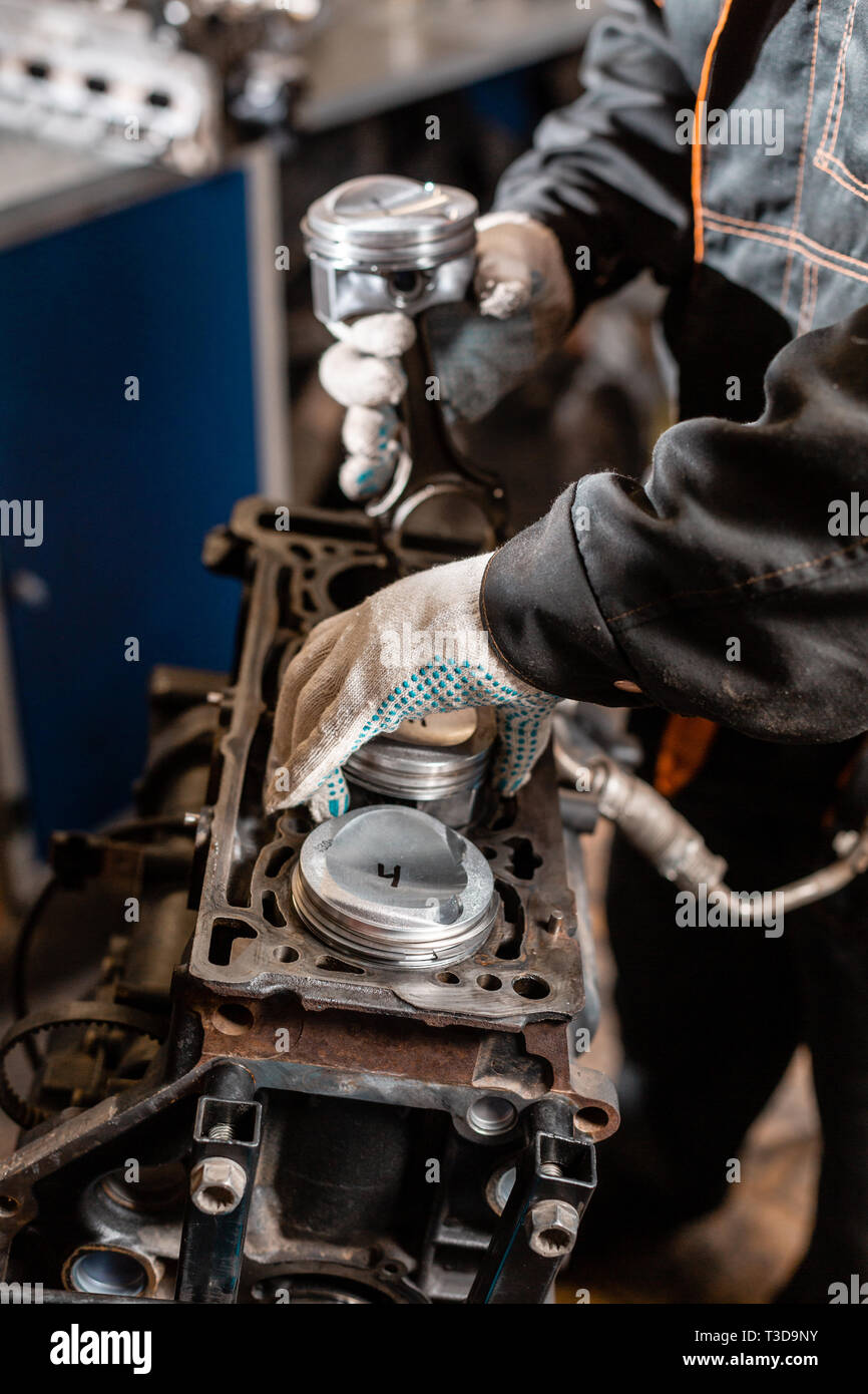 hight resolution of close up car mechanic holding a new piston for the engine overhaul engine on a repair stand with piston and connecting rod of automotive technology
