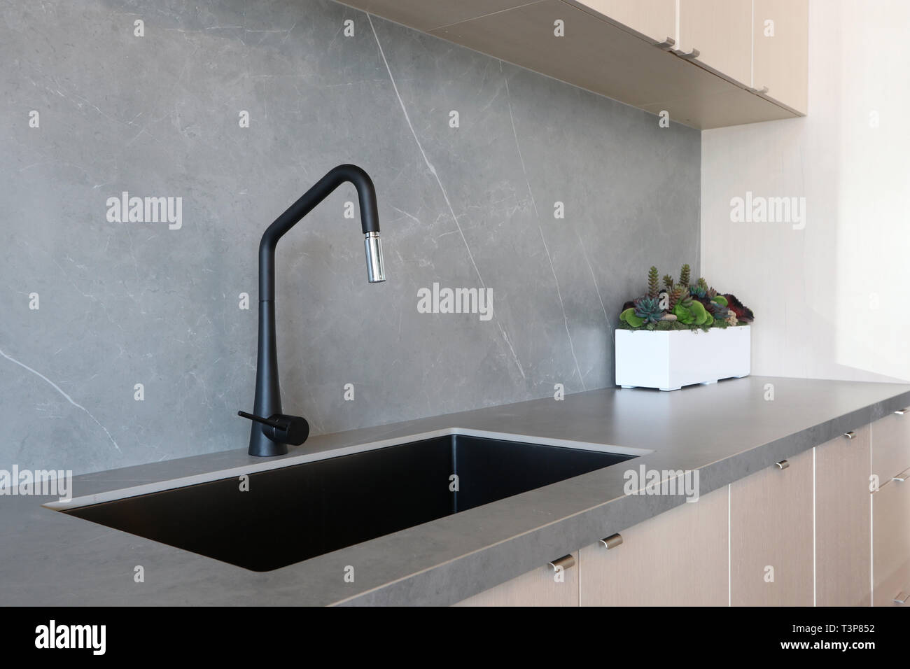 A Black Sink And Matt Finish Black Faucet Set Against A Grey Countertop And Backsplash Made Of Porcelain Slabs That Mimic The Natural Look Of Stones Stock Photo Alamy