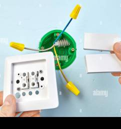 installation of new button for two button light switch round outlet box for wall light on the background  [ 1300 x 956 Pixel ]