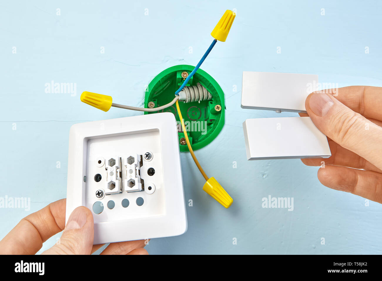 hight resolution of installation of new button for two button light switch round outlet box for wall light on the background