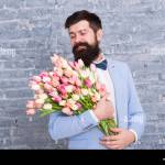 Womens Day Spring Beauty Flower For March 8 Spring Gift Bearded Man With Flowers Bearded Man With Tulip Bouquet Love Date International Holiday Happy Bearded Man Bearded Florist Man In Love Stock