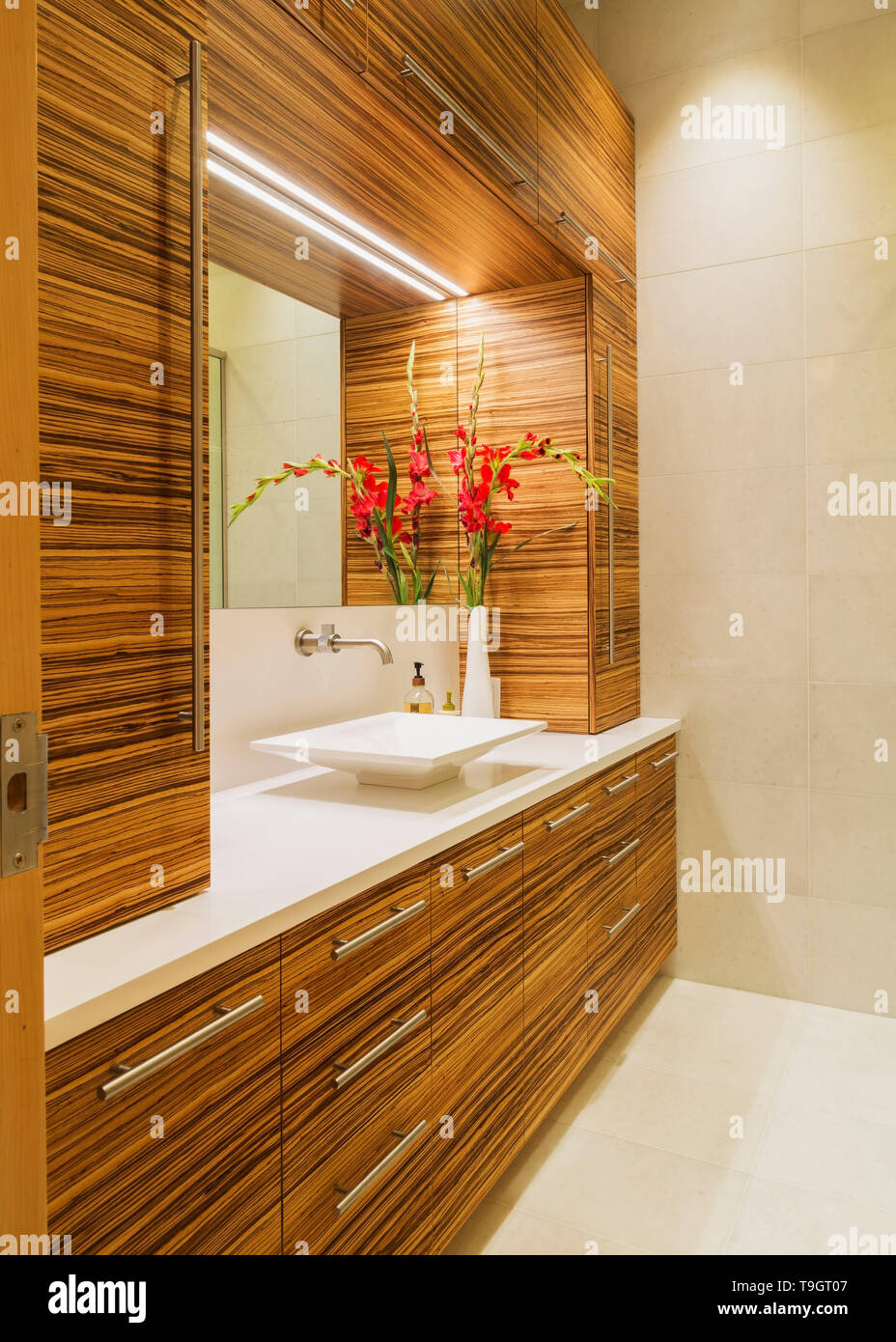 Zebra Wood Vanity With Pure White Quartz Countertop And Vessel Sink In Guest Bathroom With Marble Floor Ansd Wall Inside A Luxurious Renovated Condominium Unit In An Old 1910 Multistoried Residential Heritage