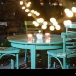 Night In The Garden Green Cafe Table With Candles And A Ashtray Stock Photo Alamy