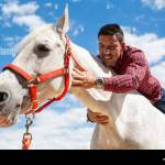 Excited Young Guy In Casual Outfit Smiling And Embracing Neck Of White Horse During Ride In Field On Cloudy Day Stock Photo Alamy