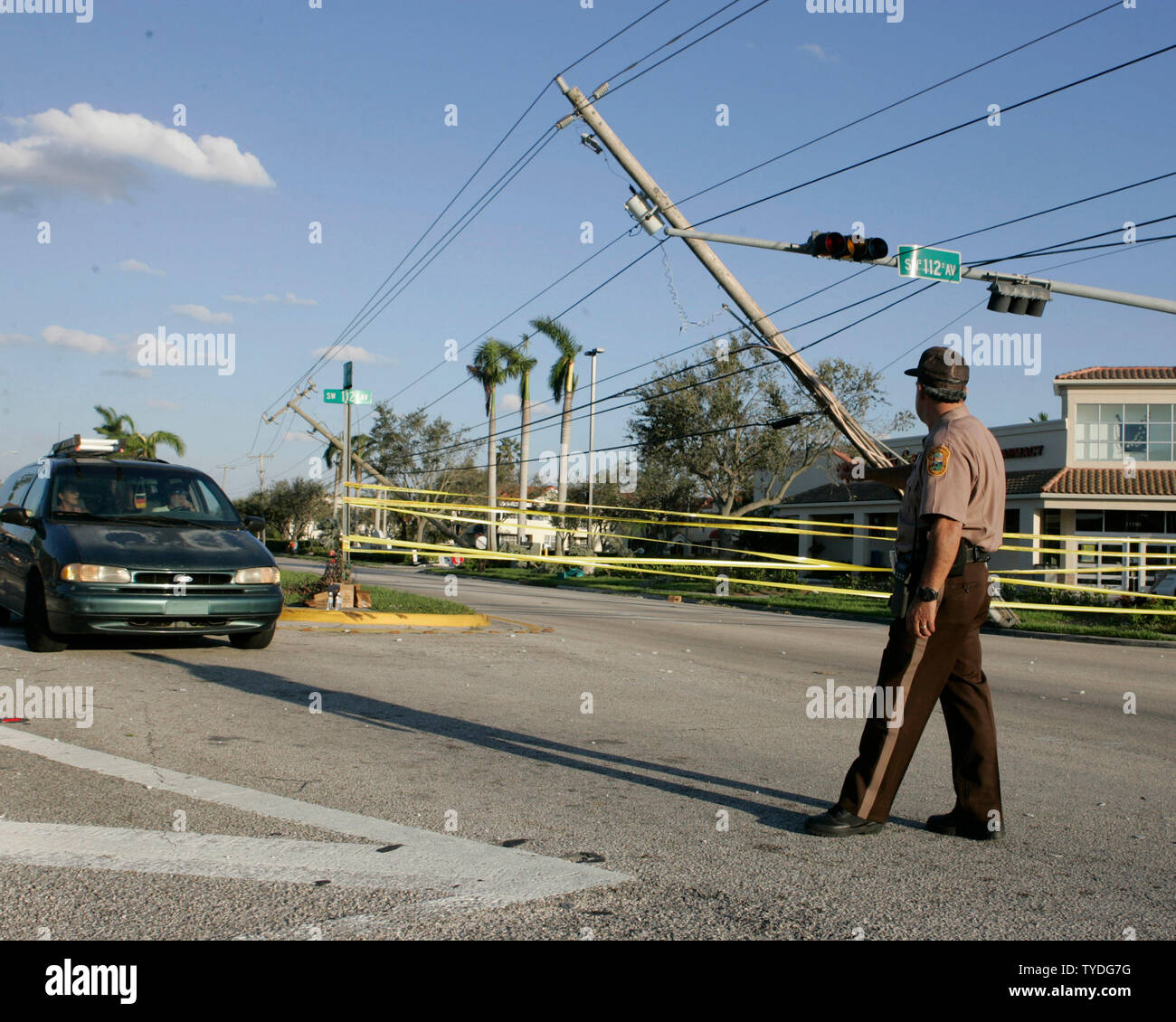 https www alamy com an officer of the miami dade police department directs traffic on kendall drive in south dade as broken power poles have one side of traffic closed in the wake of category 3 hurricane wilma in miami florida on october 25 2005 upi photomichael bush image257838996 html