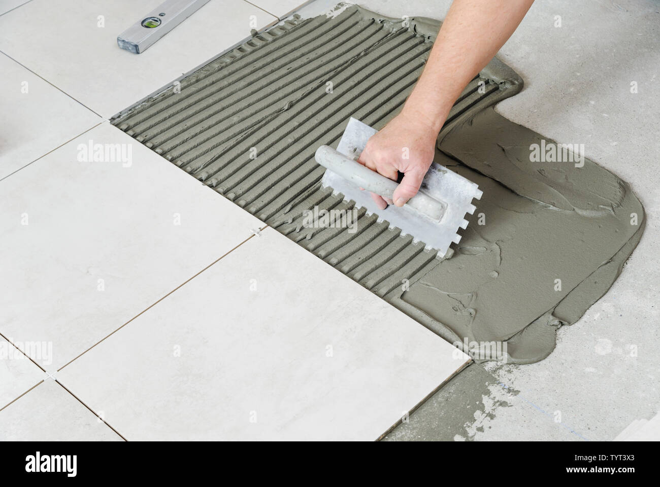 https www alamy com the workers hand is putting tiles adhesive to the wall with the notched trowel image258070795 html