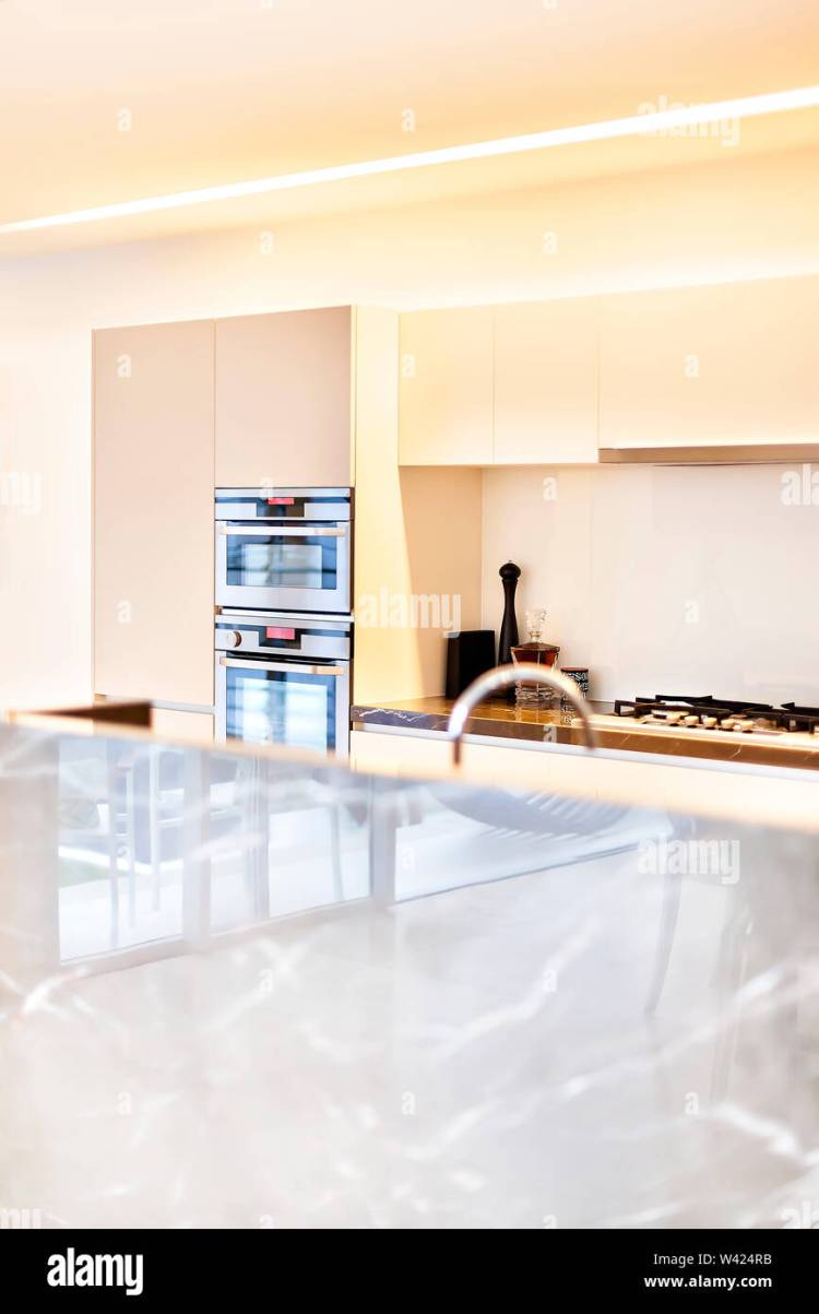 Modern Kitchen Area With Yellow Walls And Silver Ovens Beside Perfume And Metal Stove Under The Pantry Cupboard The Counter Can Be Seen Very Closely Stock Photo Alamy