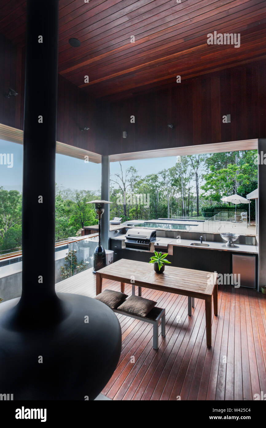 https www alamy com high angle view of a modern patio made in wooden floor and ceiling including a gas grill beside a bench there are glass windows that showed the outsi image260662308 html