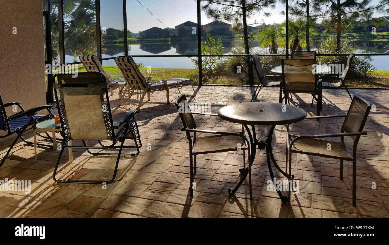 https www alamy com lanai early morning pavers patio tables chairs lounges pond view shrubs cage screening outdoor living space florida fl horizontal pr image264211688 html