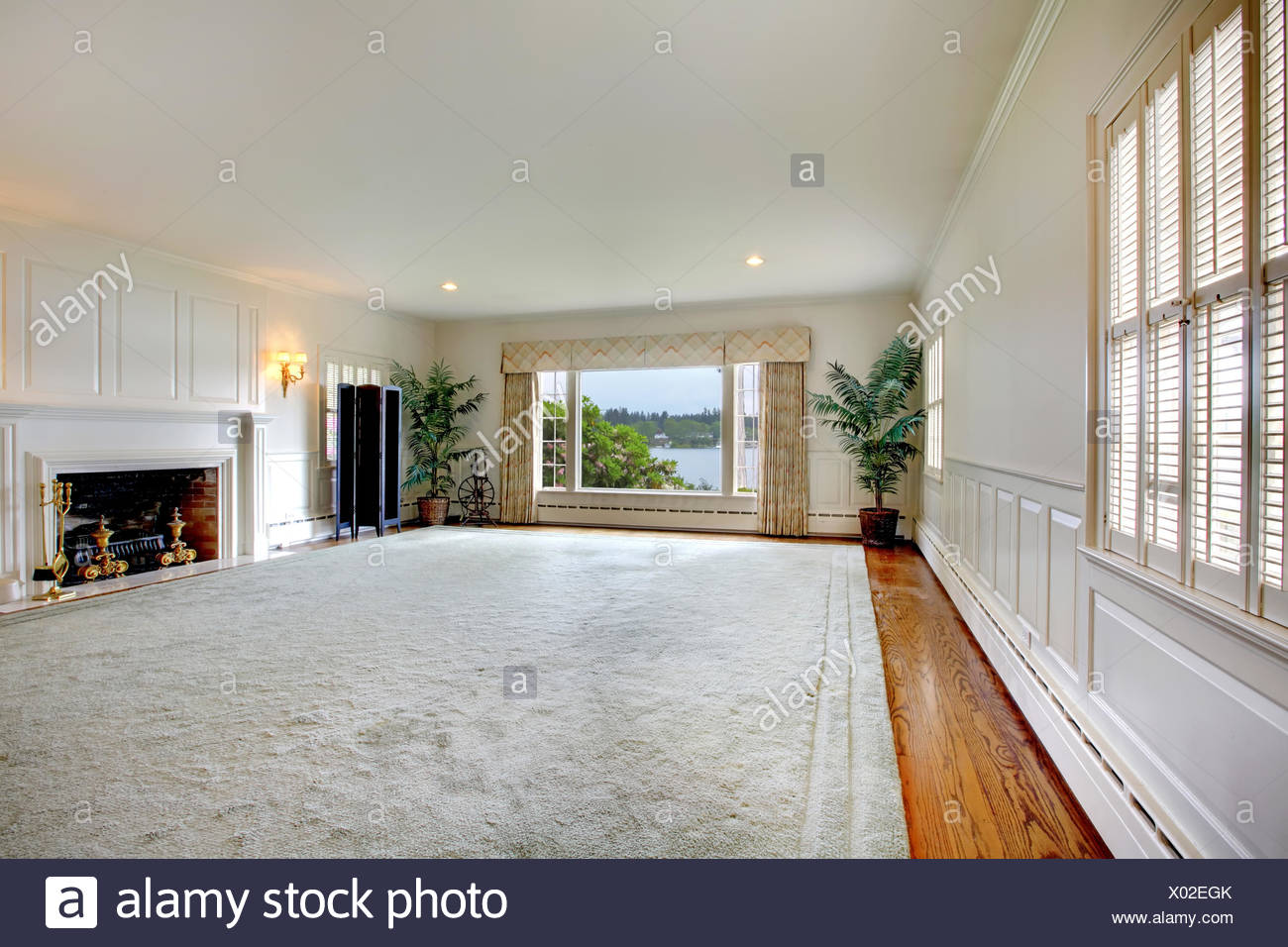 Large empty living room with fireplace and lake view Stock