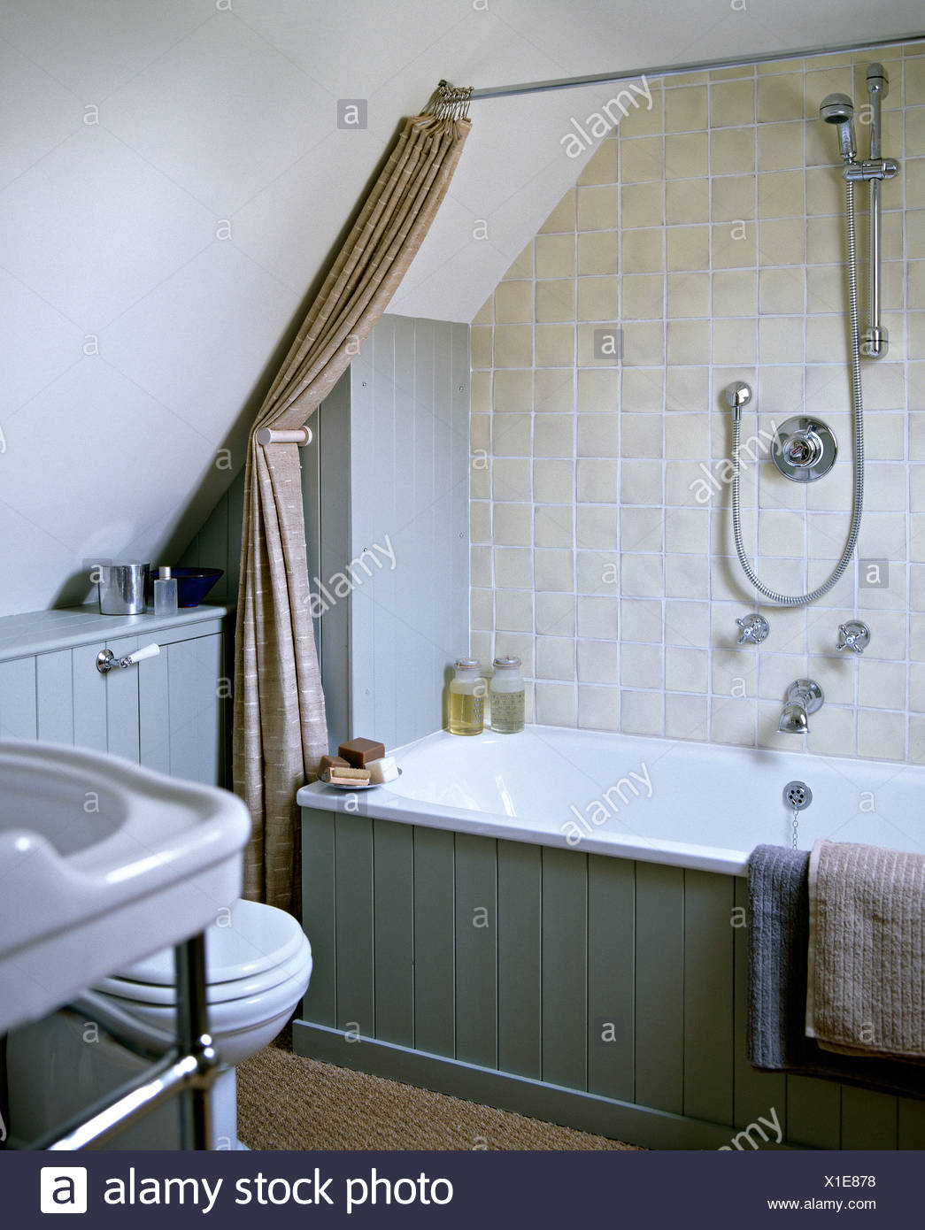 https www alamy com grey rustic tiles and chrome shower on wall above bath with tonguegroove paneling in country attic bedroom image276294348 html