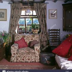 Floral Arm Chair Folding Chairs And Tables Patterned Drapes On Window Above Armchair In Cottage Living Room With Antique Ladder Back Painted Circular Box