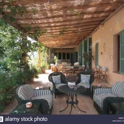 Comfortable Wicker Chairs Cast Aluminum Patio Chair Parts Rattan Roof Above Spanish Veranda With Striped Cushions On And Sofa