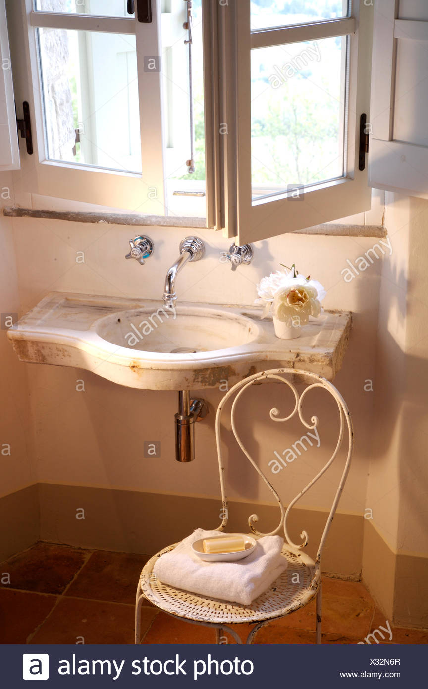 https www alamy com open windows above small wall mounted basin in italian country bathroom with a white metal vintage chair image277270415 html