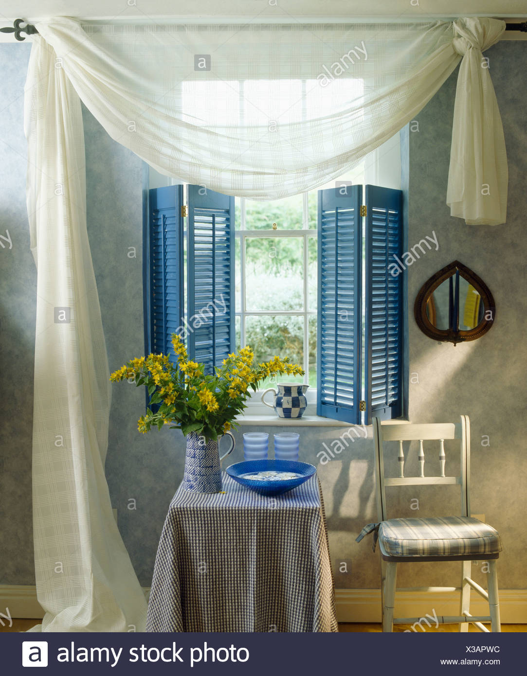 White Voile Drapes And Blue Plantation Shutters On Window