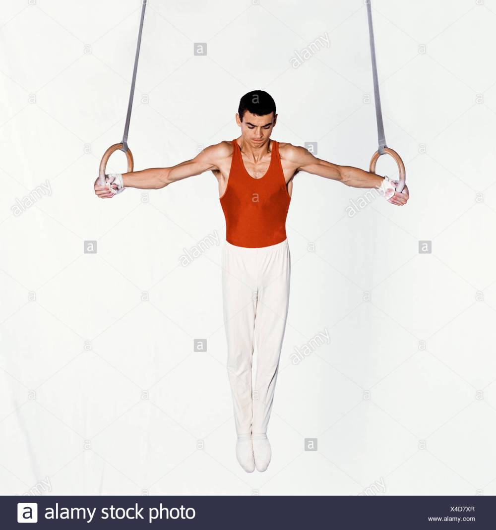 medium resolution of young male gymnast performing routine on rings stock image