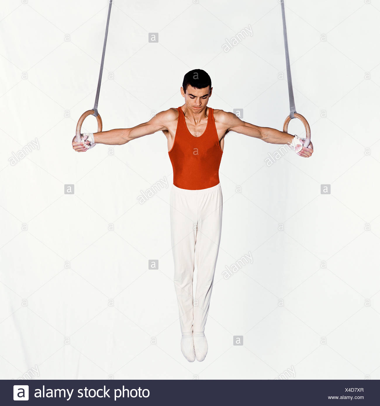 hight resolution of young male gymnast performing routine on rings stock image