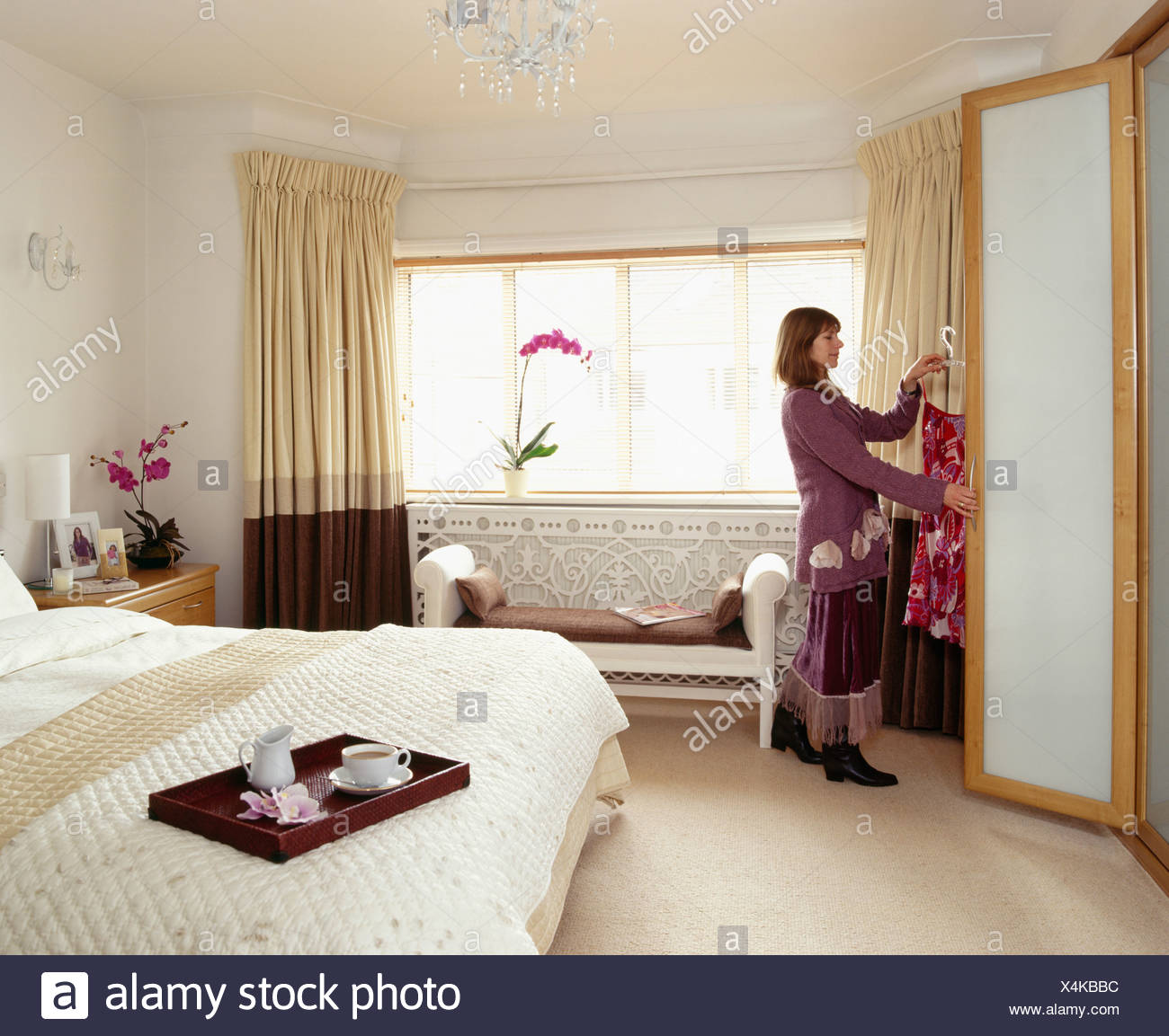 Woman Putting Clothes Into Wardrobe In Modern Cream Bedroom Stock Photo Alamy