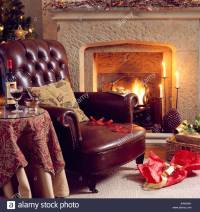 Brown leather sofa beside fireplace with lighted fire in ...