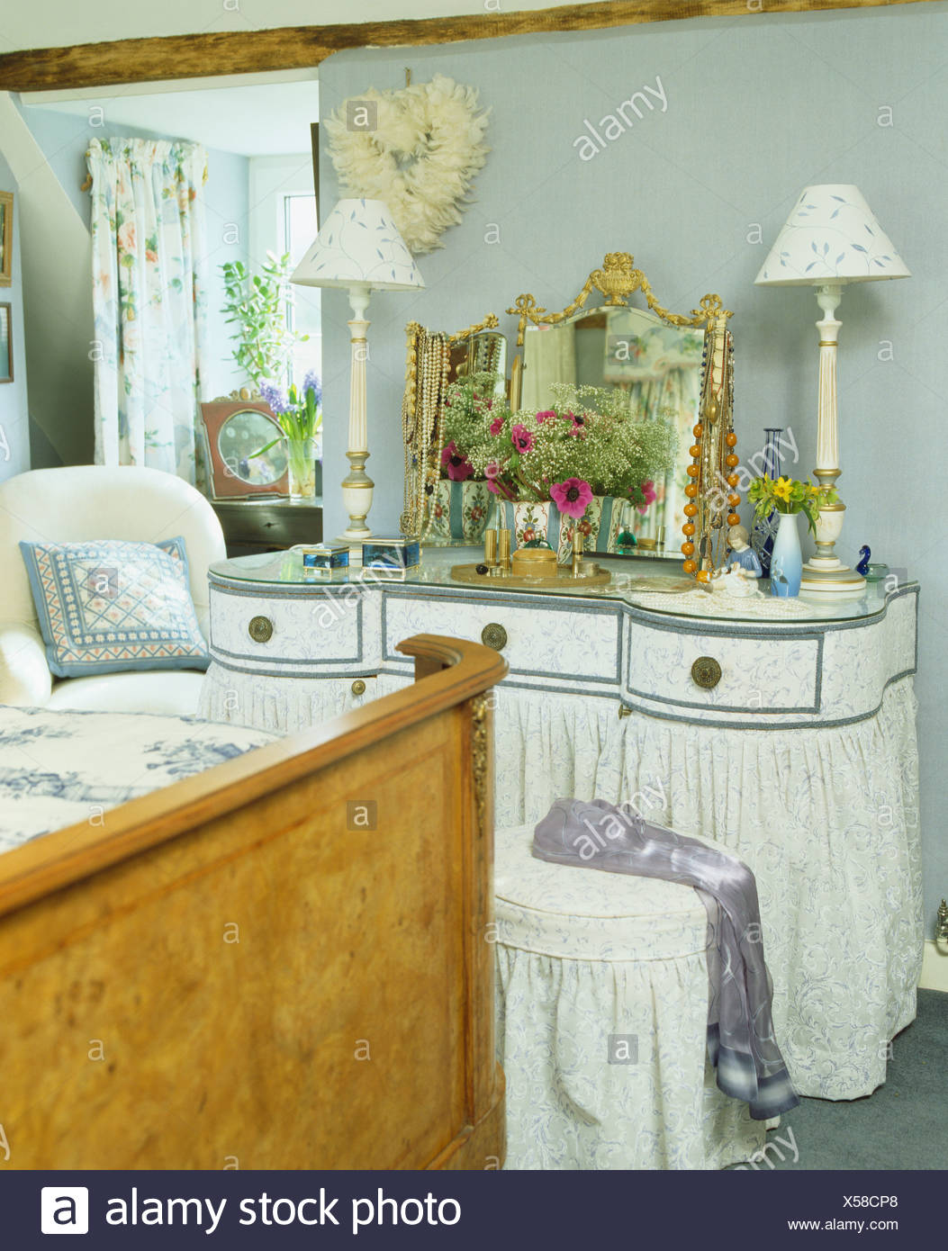 Blue Gray Cottage Bedroom With White Lamps On Dressing Table With Skirted Bernard Thorpe Drapes And Antique Mirror Stock Photo Alamy