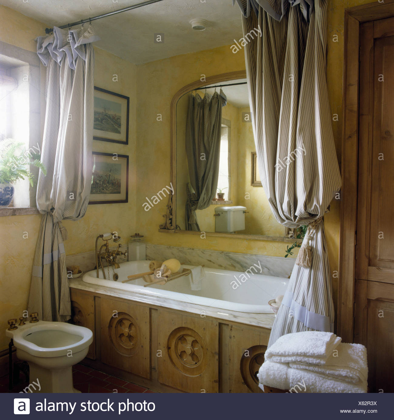 Tenda per vasca da bagno. Striped Shower Curtains On Bath With Reclaimed Carved Wood Panel In Eighties Bathroom With A Bidet Stock Photo Alamy