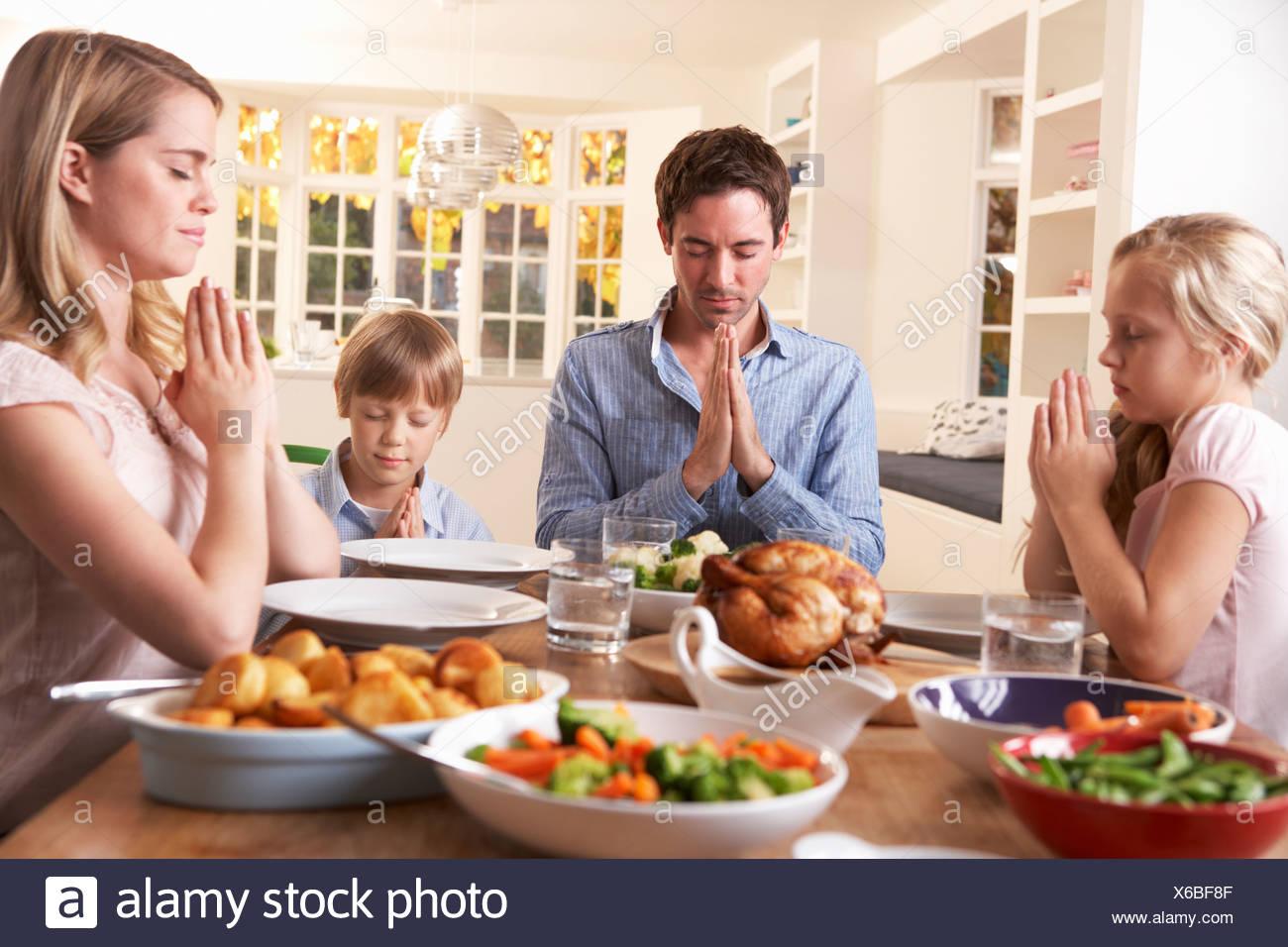 family saying prayer before