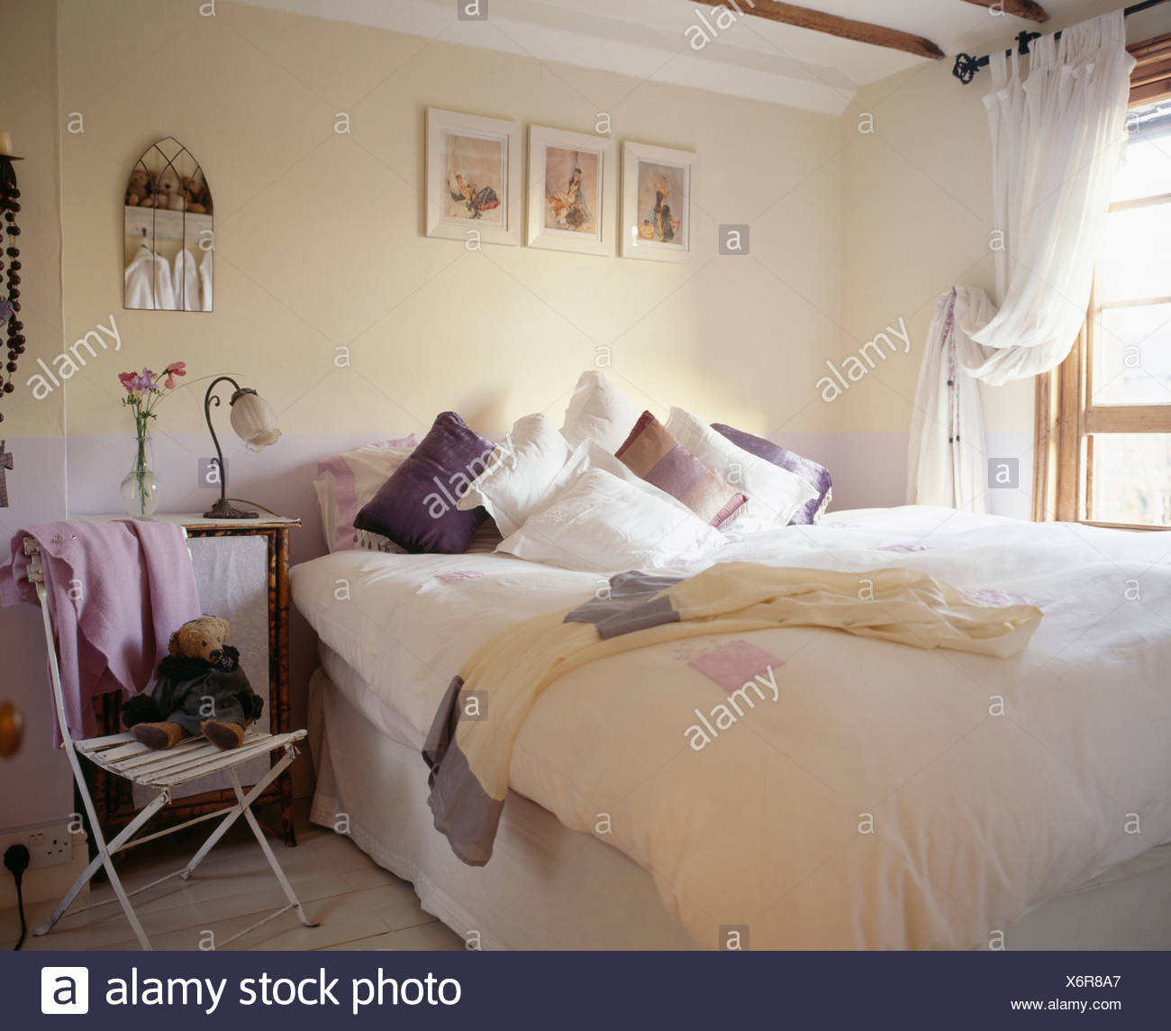 bedroom chair for clothes swing daraz bed piled with pillows in cream country thrown over small metal beside