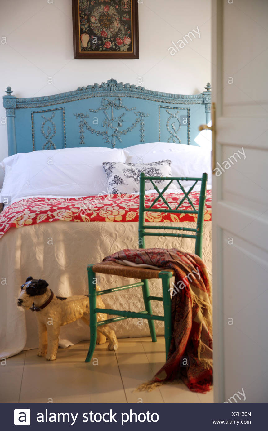 Toy Dog Beside Painted Chair In French Country Bedroom With White Quilt And Red Floral Throw On Blue Painted Bed Stock Photo Alamy