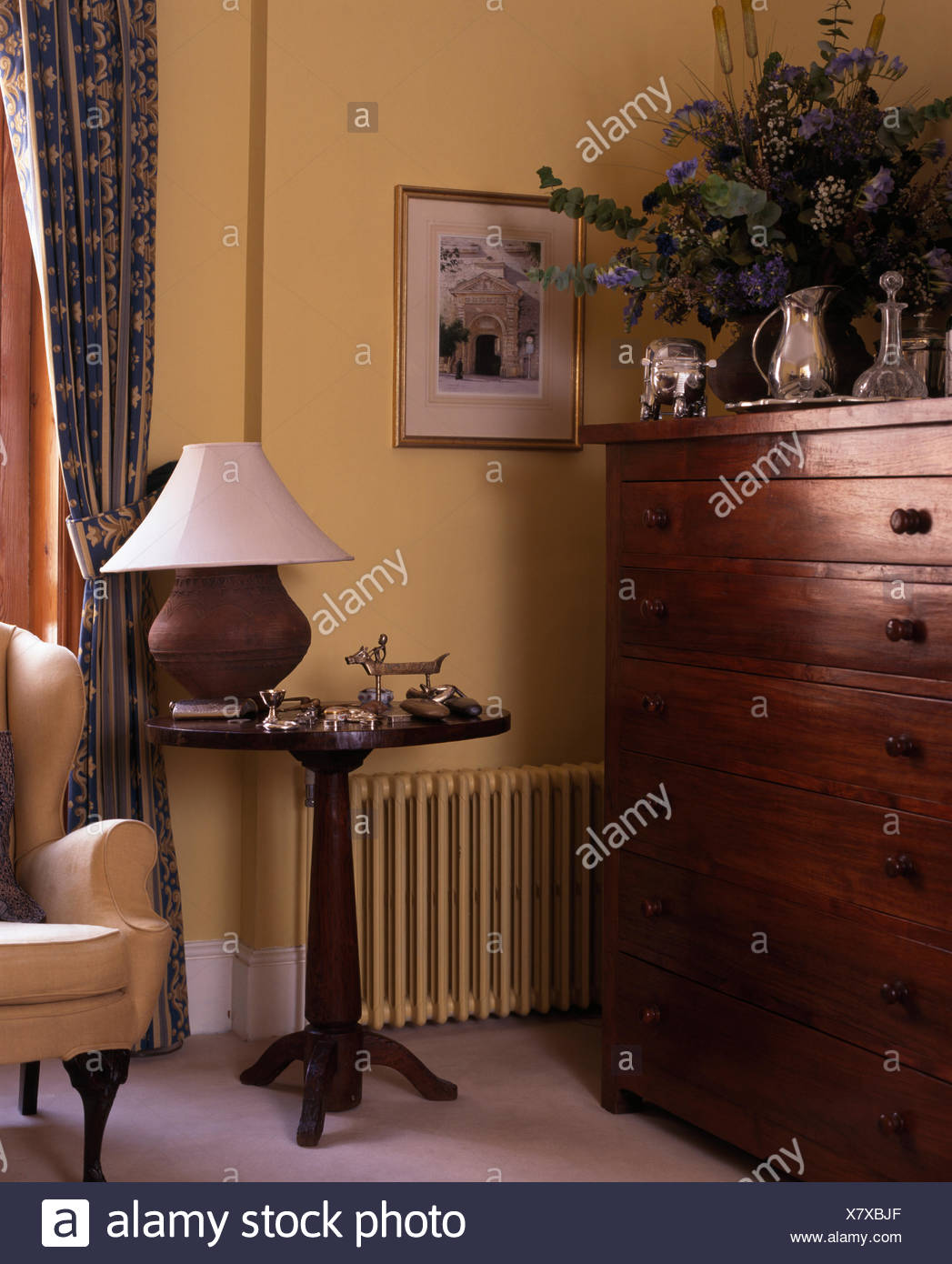 https www alamy com earthenware lamp on antique side table in corner a traditional living room with a vintage chest of drawers image280248375 html