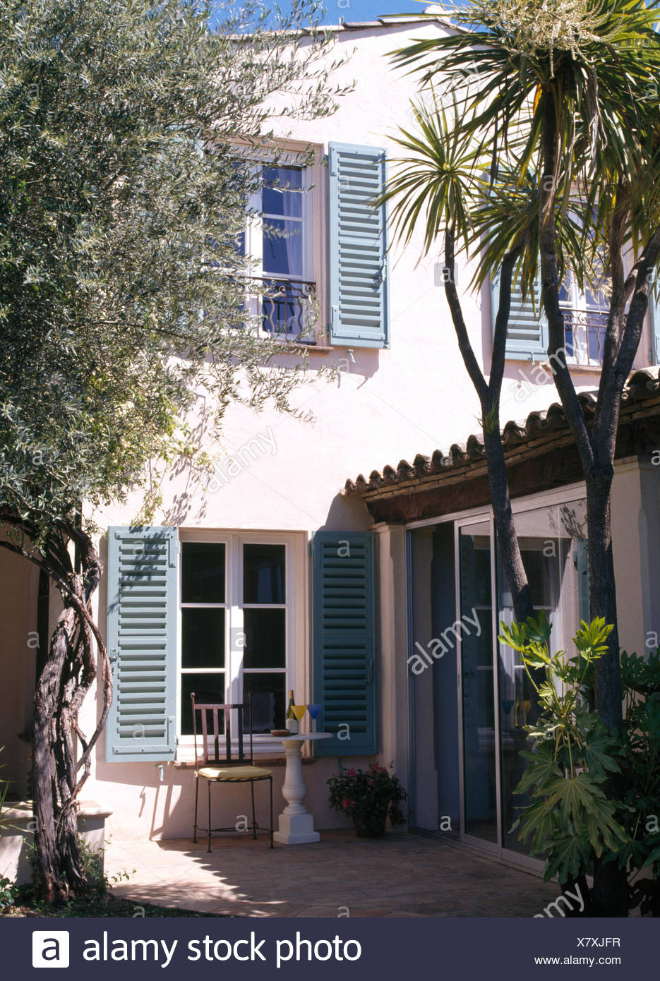 Exterior Of French Country Villa With Pale Blue Shutters