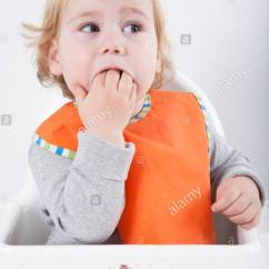 Age For High Chair Nathan Teak Dining Chairs Uk Blonde Caucasian Baby Seventeen Month Orange Bib Grey Sweater Eating Meal In White Surprised Looking At Carrot And Tuna