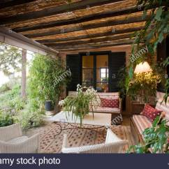 Veranda Living Rooms Side Bench For Room Comfy Sofas And White Lloyd Loom Chairs Oin Outdoor On Rustic With Lush Plants Patterned Rug