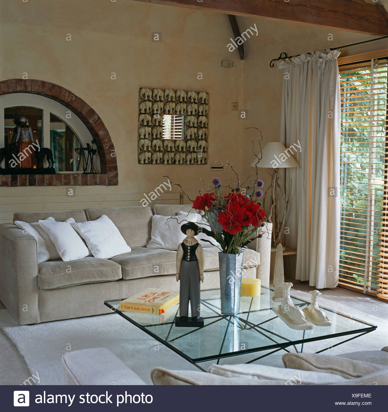 https www alamy com wooden figure and vase of red roses on glass coffee table in modern living room with gray velour sofa and cream curtains image281238622 html