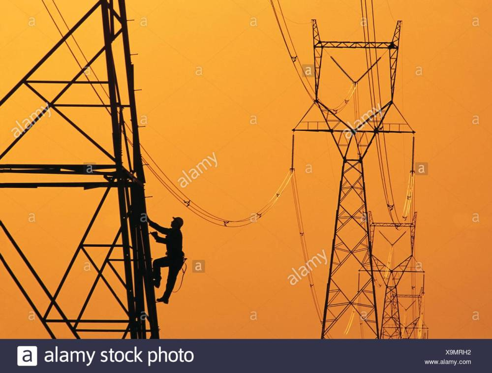 medium resolution of a worker climbs an electrical tower manitoba canada stock image
