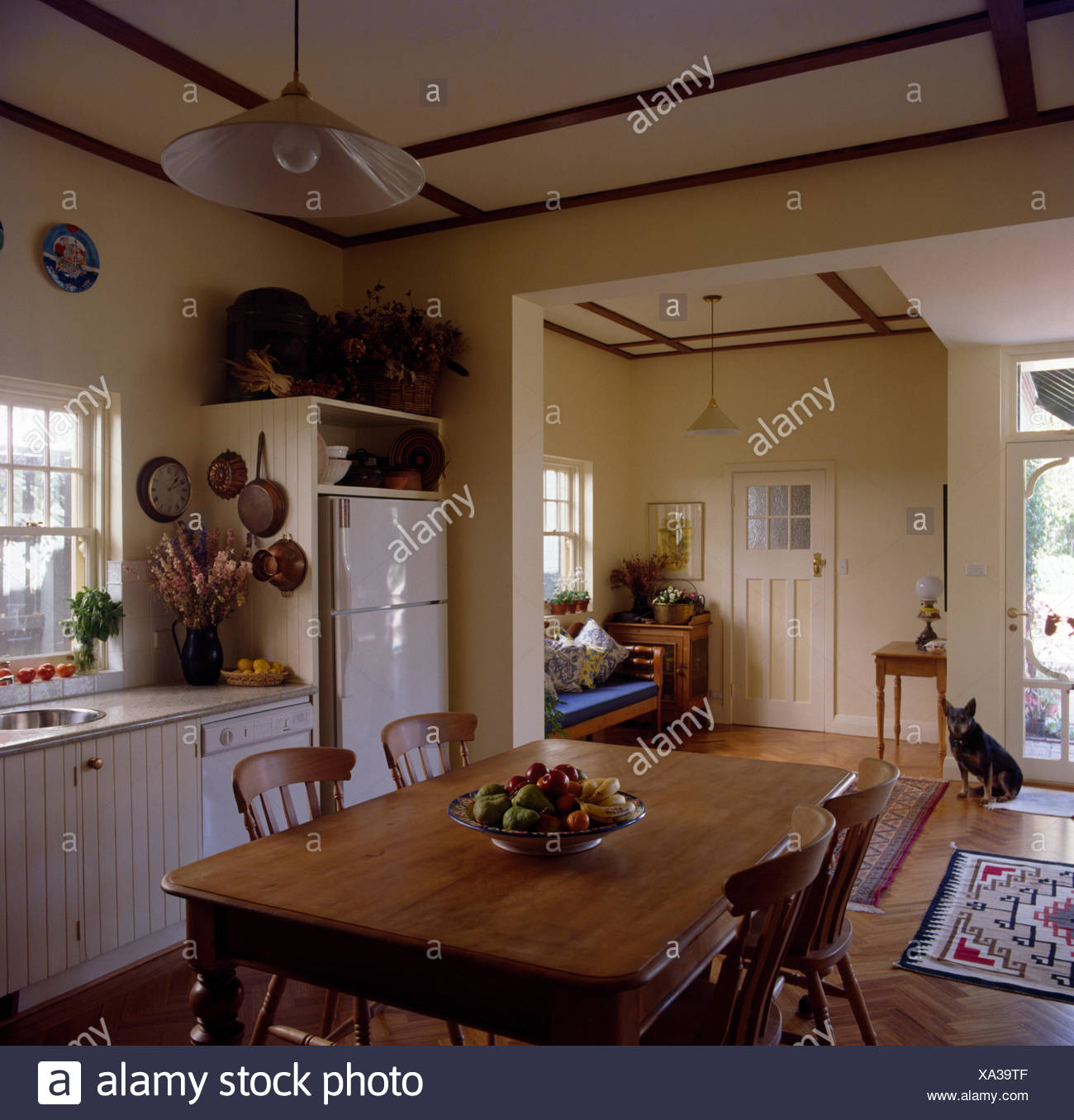 Vintage Pine Table And Chairs In An Open Plan Traditional Kitchen With A Dog Sitting Beside The Front Door Stock Photo Alamy