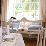 Blue Striped Cushion On White Settle In Front Of Window With White Linen Curtains In Dining Room With White Cloth On Table Stock Photo Alamy
