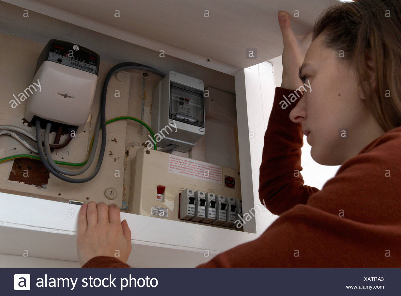 hight resolution of woman checking electric meter uk