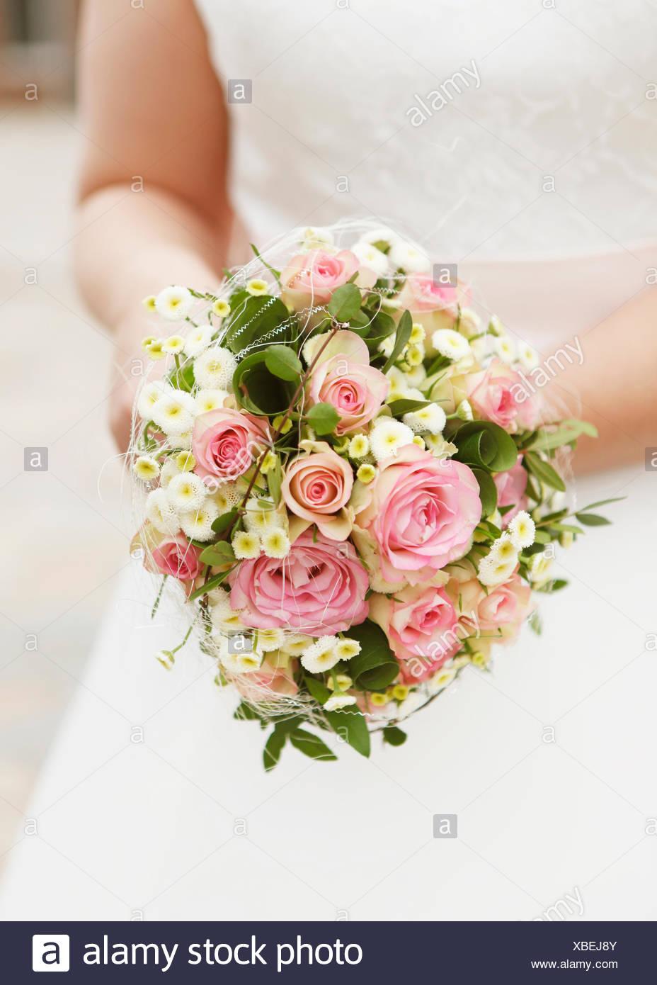 eine Braut mit Brautstrau rosa Rosen kein Gesicht Stock