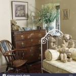 Teddy Bear And Yellow Checked Bolster On White Iron Day Bed In Cottage Bedroom With Antique Chest Of Drawers And Windsor Chair Stock Photo Alamy