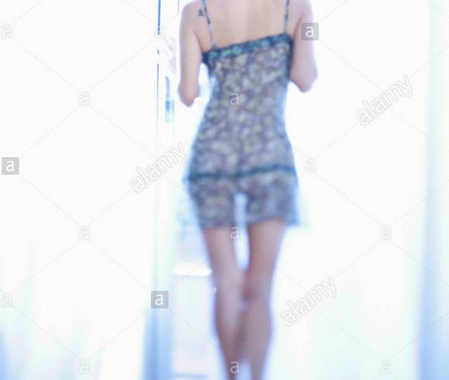 Rear View Of A Woman In See Through Nightgown Looking Out A Window Stock Image