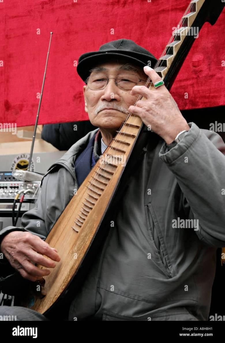 ein alter mann spielt traditionelles instrument an das chinesische