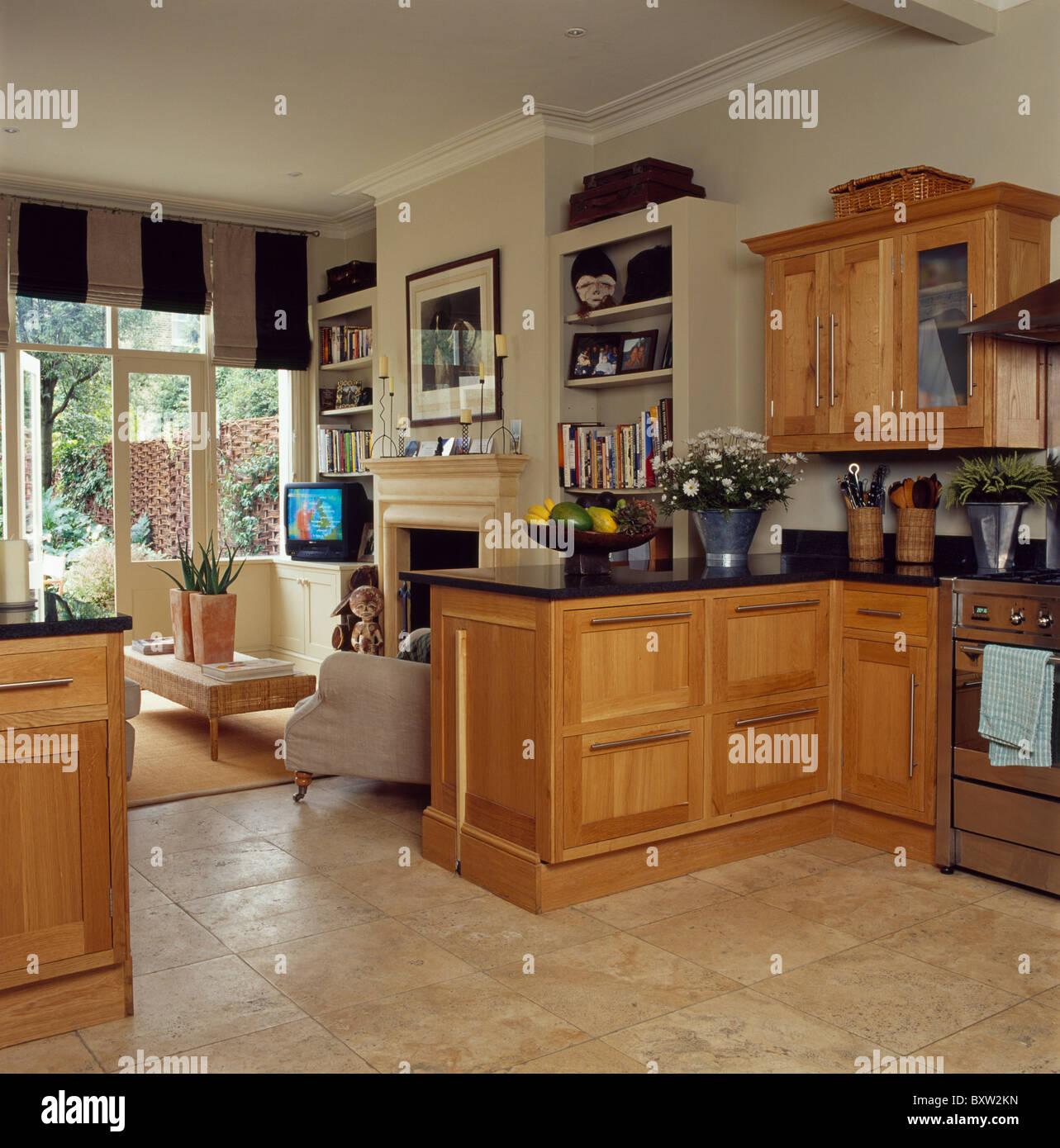 Kalkstein Bodenbelag und blasse Holz Einheiten in die offene Kche und Wohnzimmer mit Schwarz