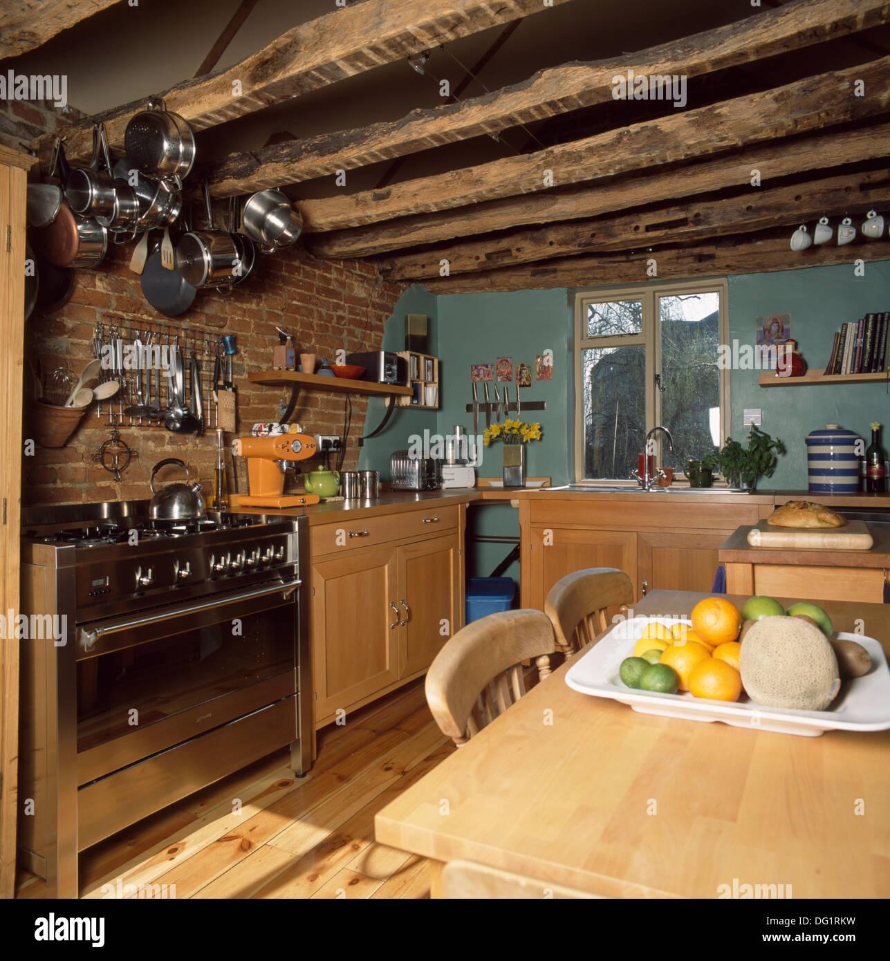 pfannen auf rack uber edelstahl herd im landhaus kuche mit rustikalen holzbalken und kiefer tisch