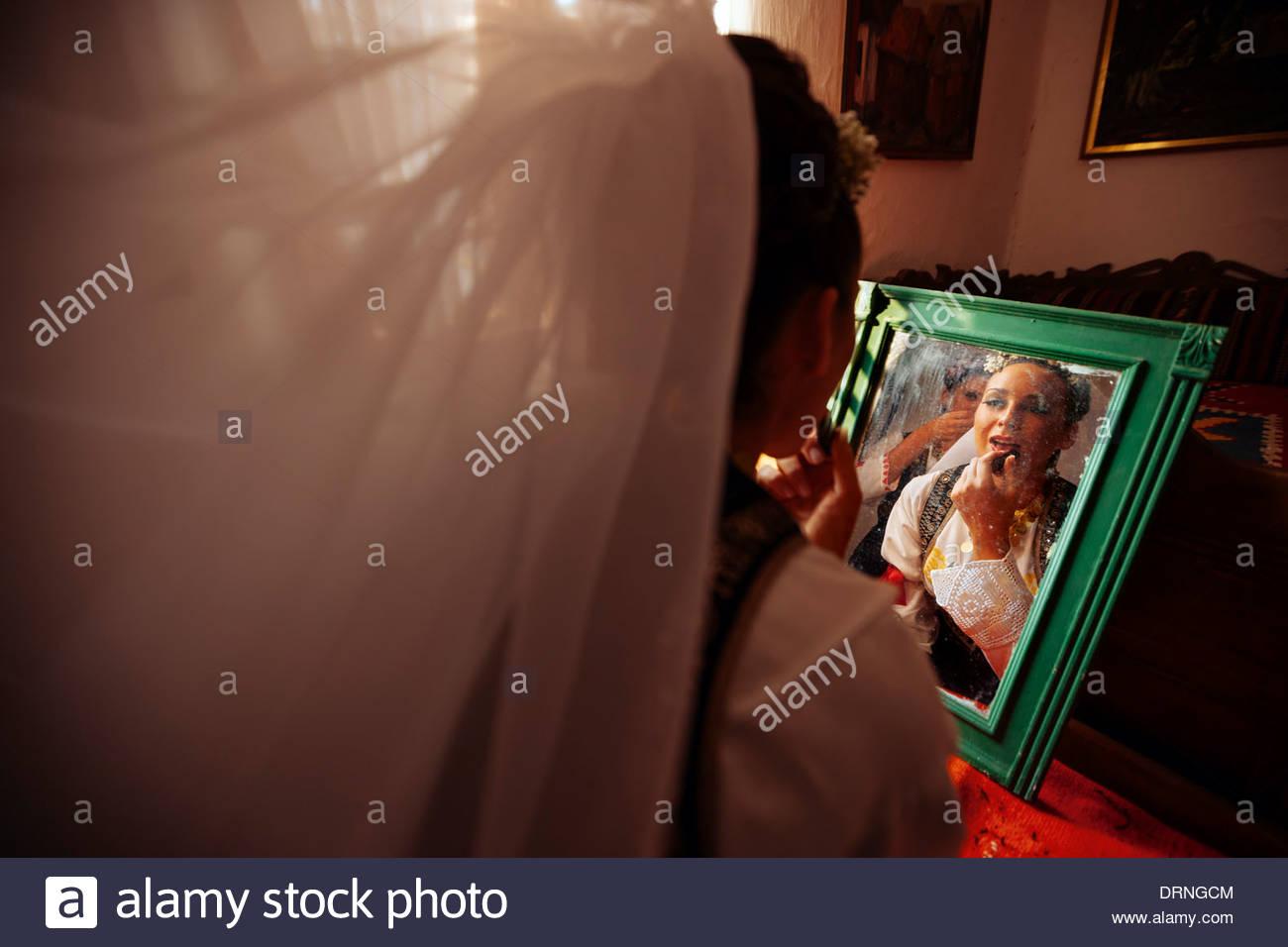 Serbische Braut setzt Lippenstift vor dem Spiegel