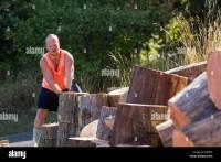 junger Mann im freien Spalten Holz von hand fr die wirer ...